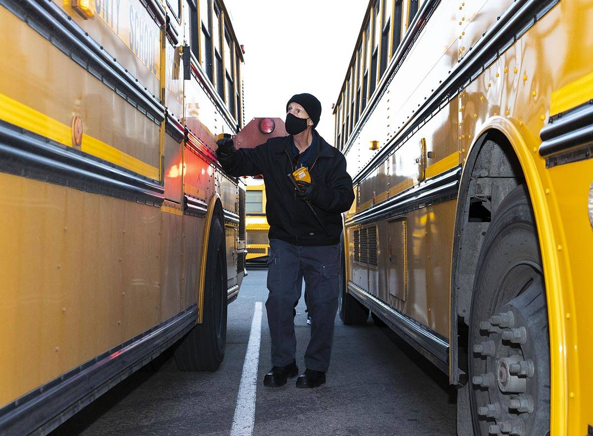 Donald Brace, a school bus driver, inspects his bus as he prepares to head out to pick up stude ...
