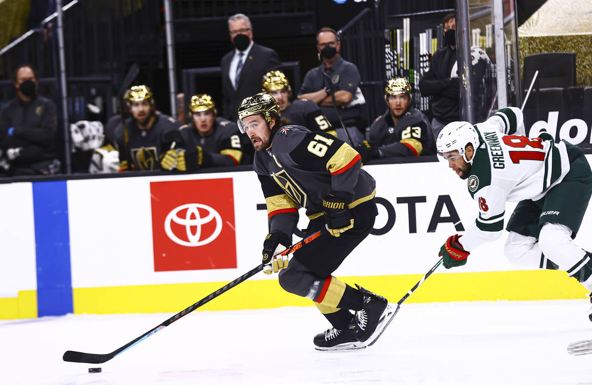 Golden Knights right wing Mark Stone (61) skates with the puck past Minnesota Wild left wing Jo ...