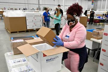 An employee with the McKesson Corporation packs a box of the Johnson and Johnson COVID-19 vacci ...