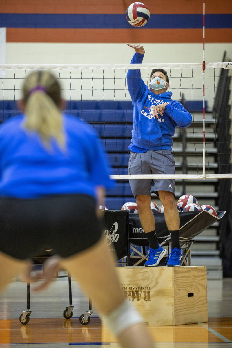 Varsity girls volleyball coach Gregg Nunley serves a ball to players during practice at Bishop ...