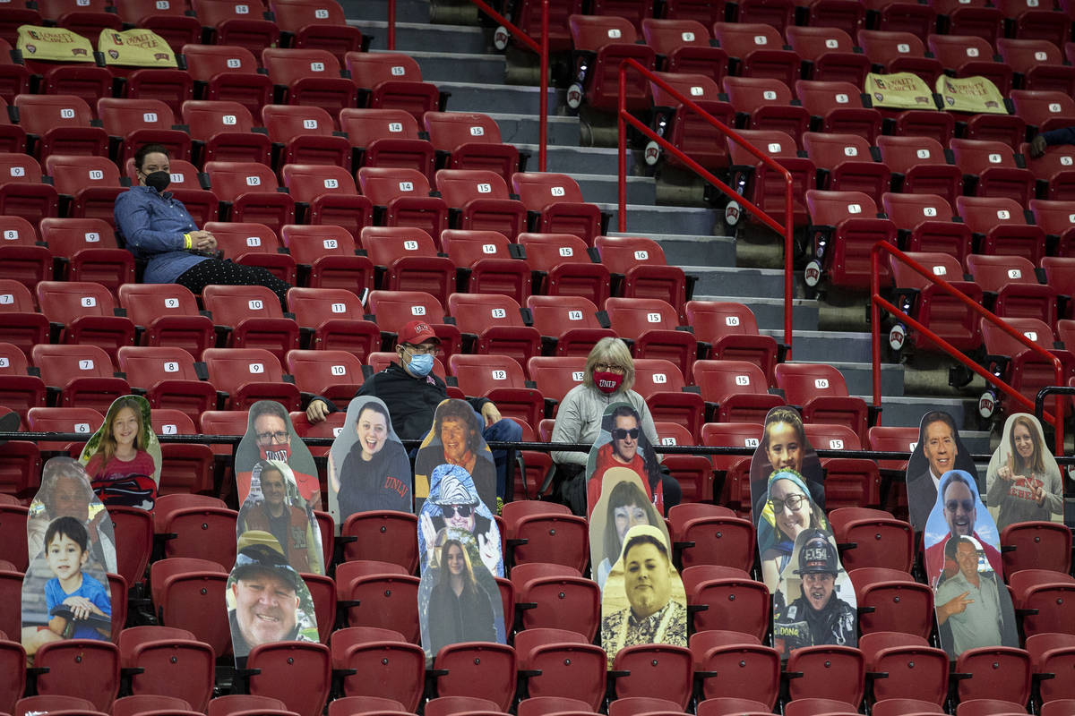 Fans sit in distances seats during the second half of an NCAA men's basketball game between the ...
