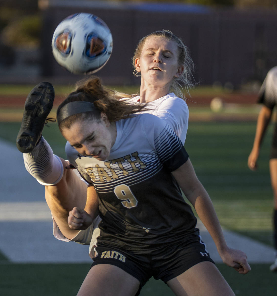 Faith Lutheran's Claire Dalbec (9) has a ball kicked past her head by Bishop Gorman's Michelle ...