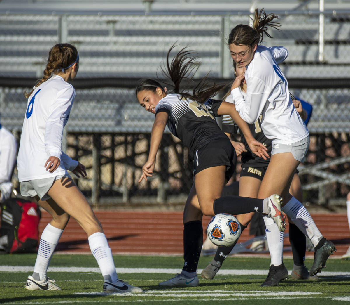 Faith Lutheran's Aurrianna Parker (21, center) fights for the ball with Bishop Gorman's Rachel ...