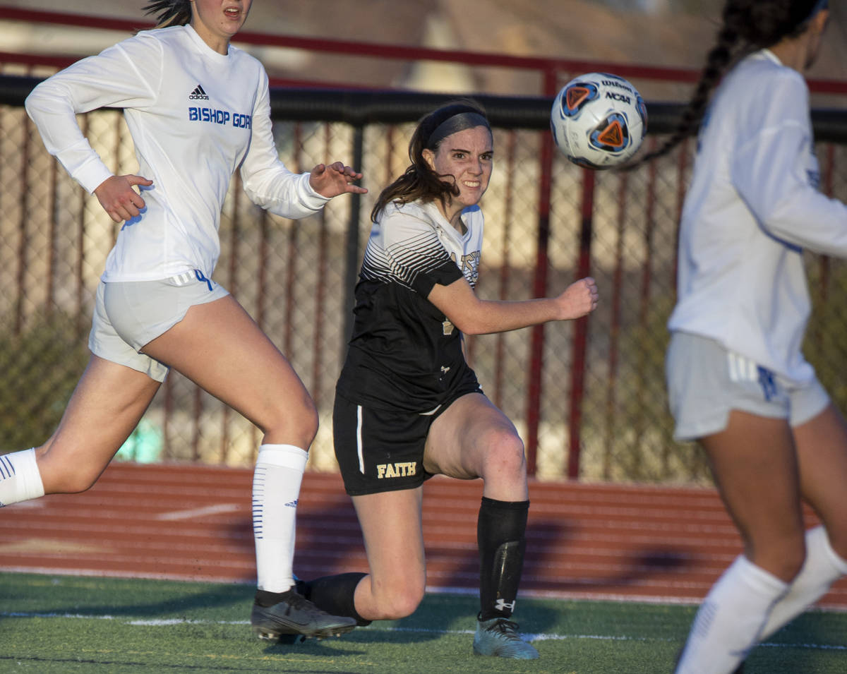Faith Lutheran's Claire Dalbec (9) drives the ball towards the goal with Bishop Gorman defender ...