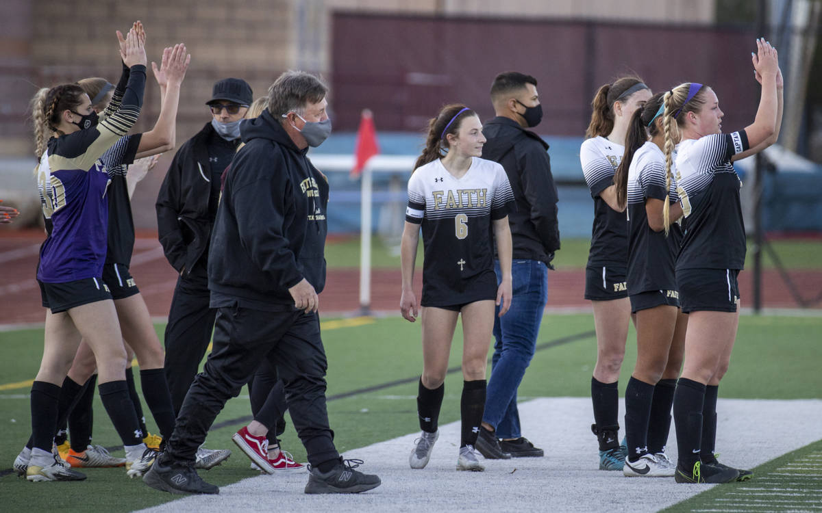 Faith Lutheran head coach Bob Chinn and players applaud the play of Bishop Gorman after winning ...