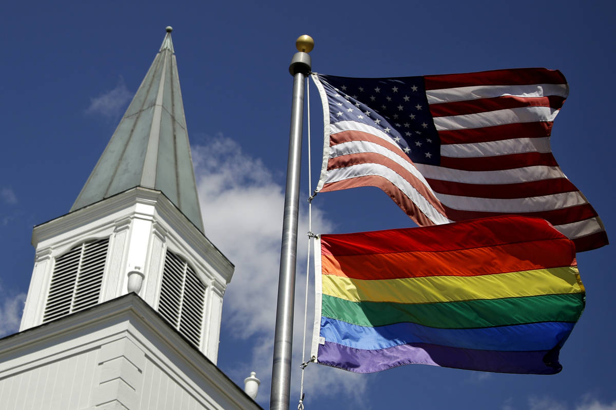 FILE - In this April 19, 2019 file photo, a gay pride rainbow flag flies along with the U.S. fl ...