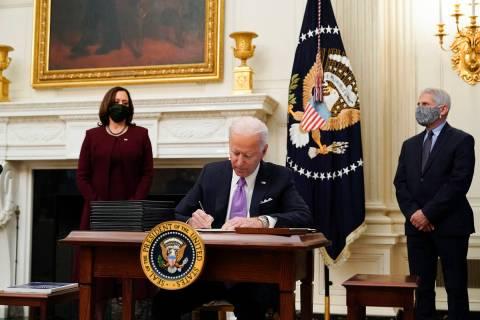President Joe Biden signs executive orders. (AP Photo/Alex Brandon)