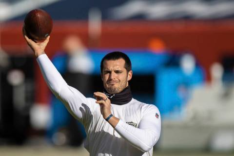 Raiders quarterback Derek Carr warms up before the start of an NFL football game against the De ...