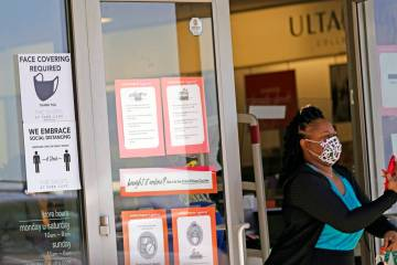 A customer exits a store with a mask required sign displayed, Tuesday, March 2, 2021, in Dallas ...