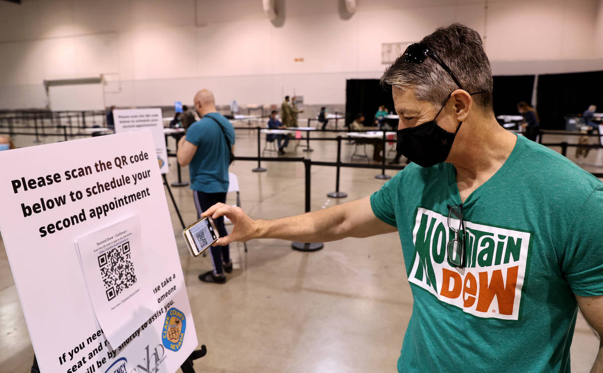 Pat McKeever, 53, who is a pilot with Southwest Airlines, scans the QR Code for his second appo ...