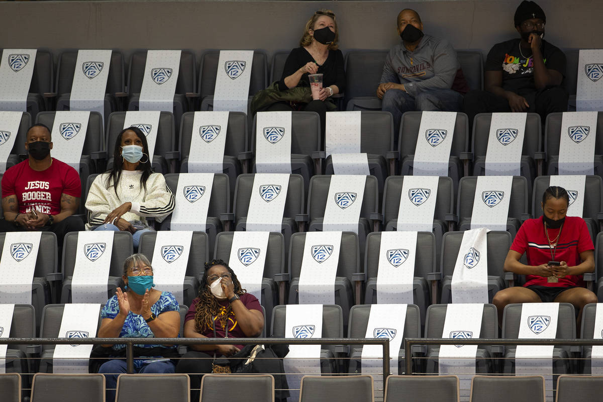 Fans sit socially distanced while watching the first half of an NCAA college basketball game be ...