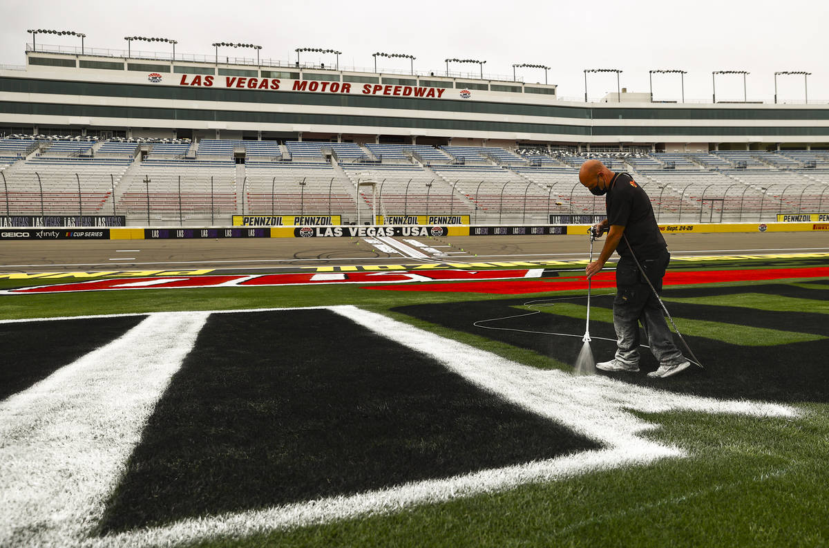 Dale Pantelakis, of Ananta Surfaces, paints logos on the infield grass ahead of the Pennzoil 40 ...
