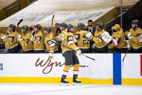 Golden Knights right wing Alex Tuch (89) is congratulated by the team after scoring the first g ...