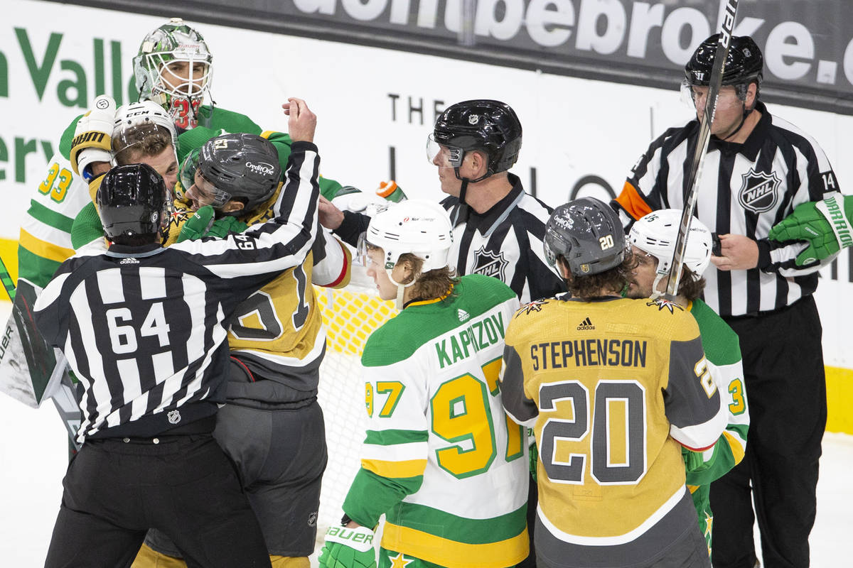Golden Knights left wing Max Pacioretty (67) and Wild defenseman Carson Soucy (21) fight during ...