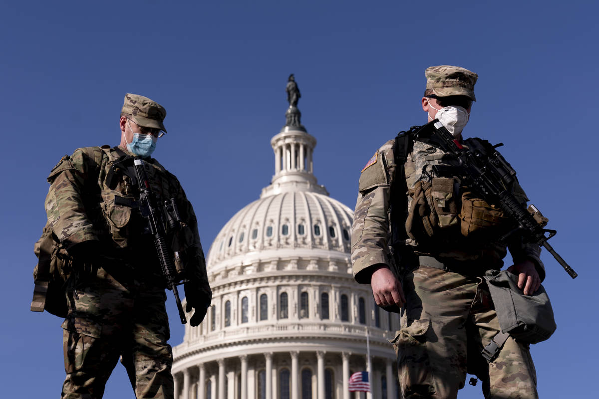 Members of the National Guard walk past the Dome of the Capitol Building on Capitol Hill in Was ...