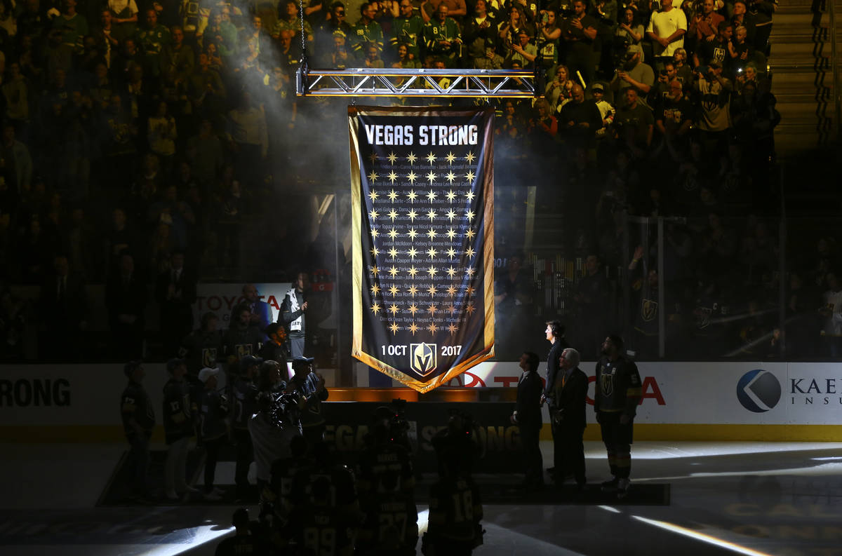A banner is raised in honor of the victims of the shooting before the start of an NHL hockey ga ...