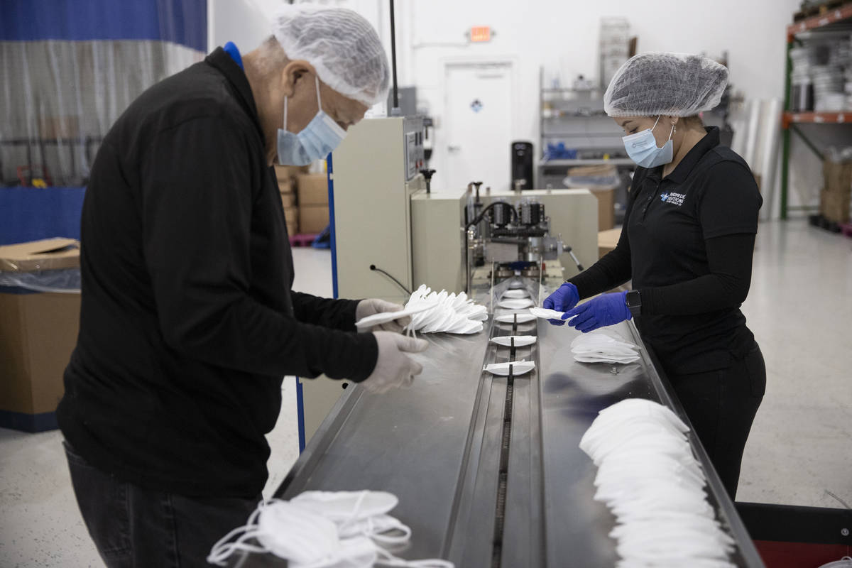 Manufacturing technicians Homar Luna, left, and Angelica Aguas check the quality of N95 masks a ...