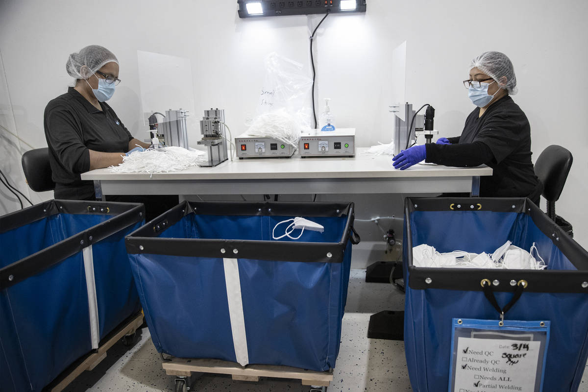 Manufacturing technicians Guillermina Sanchez, left, and Carolina Flores attach strings on N95 ...