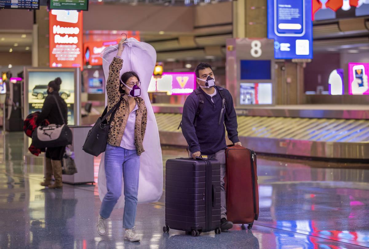 Erica Lee, left, and fiance Robert Izuta of Omaha make their way through McCarran International ...