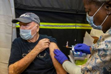 Veteran Jack Daughtrey, left, receives a shot from RN Francine Jones-Toliver as some of the fir ...