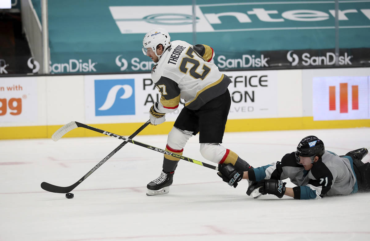 Vegas Golden Knights defenseman Shea Theodore (27) moves the puck down the ice next to a fallen ...