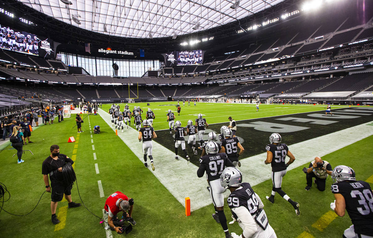 Las Vegas Raiders players run on to the field for the start of their home opening NFL game agai ...