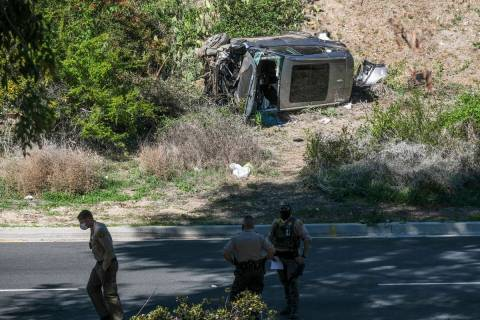 A vehicle rests on its side after a rollover accident involving golfer Tiger Woods along a road ...