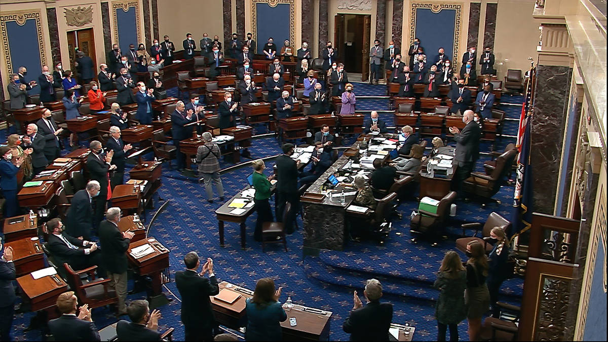 In this image from video, senators stand and applaud support staff, before the final vote on th ...