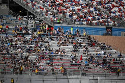 Fans watch the action during the NASCAR Cup Series Pennzoil 400 auto race at the Las Vegas Moto ...