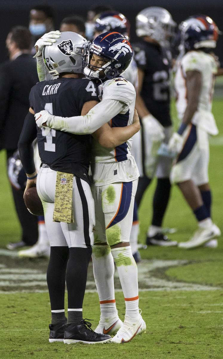 Las Vegas Raiders quarterback Derek Carr (4) hugs Denver Broncos cornerback A.J. Bouye (21) aft ...
