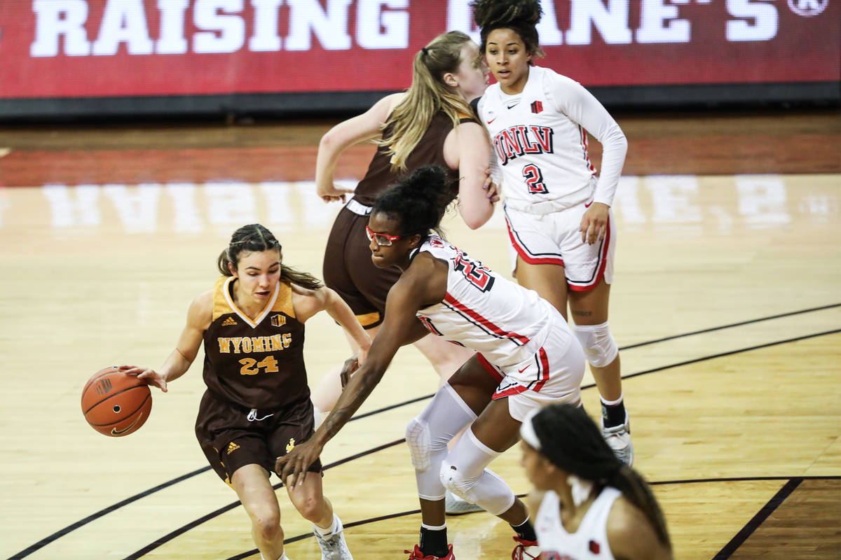 Wyoming guard Tommi Olson (24) dribbles past UNLV center Desi-Rae Young (23) in the second half ...