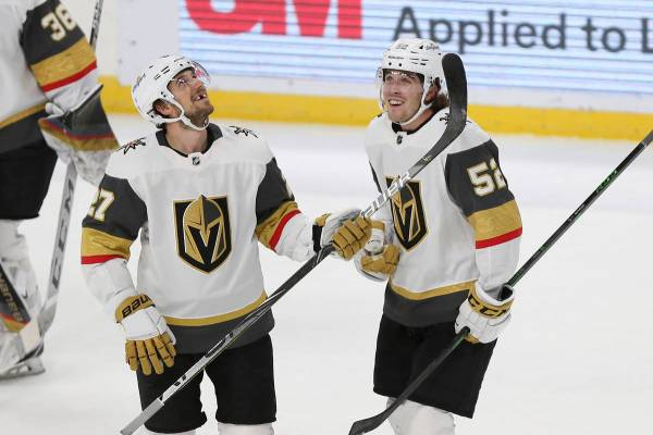 Vegas Golden Knights' Dylan Coghlan (52) smiles with his teammate Shea Theodore (27) after Cogh ...