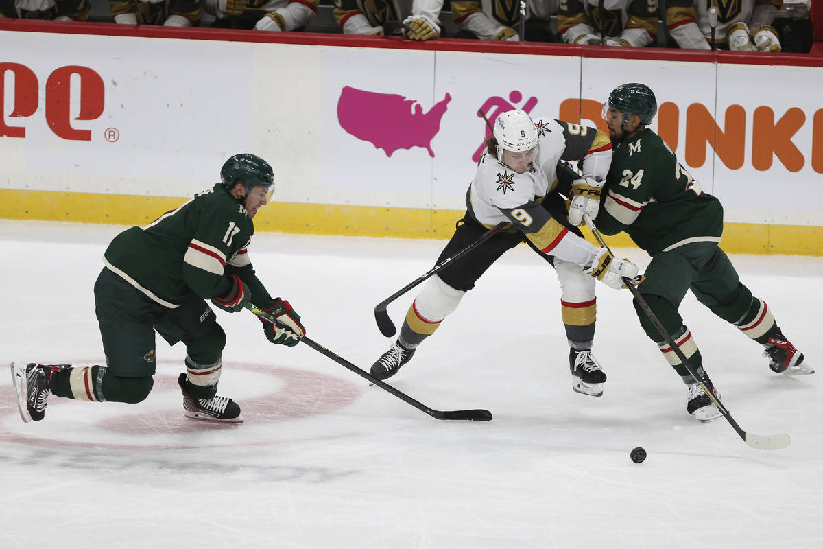 Vegas Golden Knights' Cody Glass (9) tries to gain control of the puck against Minnesota Wild's ...