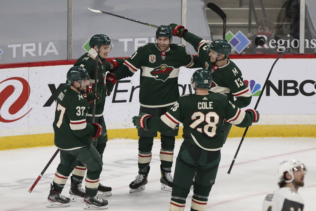 Minnesota Wild's Carson Soucy (21), center, celebrates with teammates on the ice after he score ...