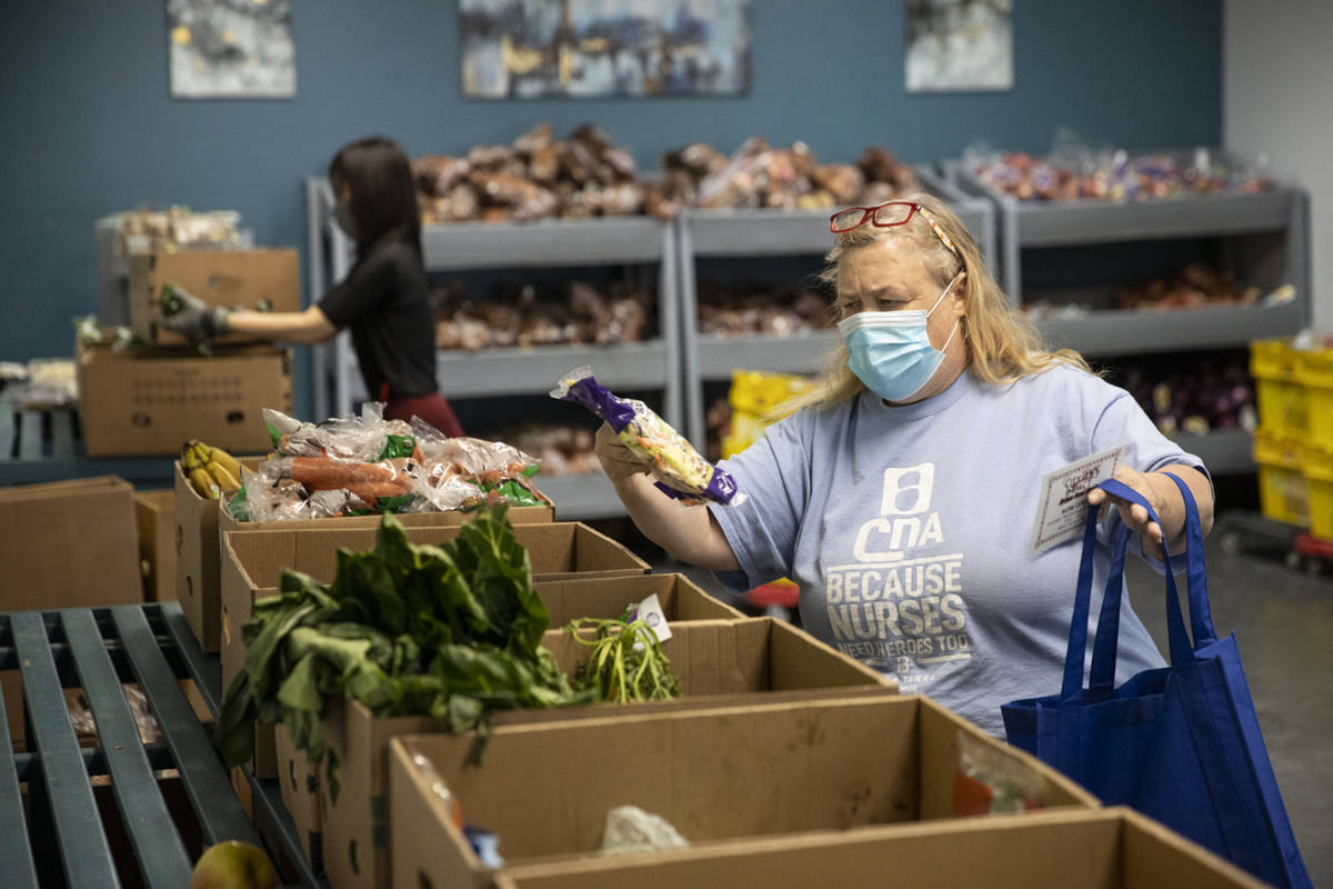 Roxann Putscher selects produce at the City Impact Urban Food Bank in Las Vegas, on Wednesday, ...
