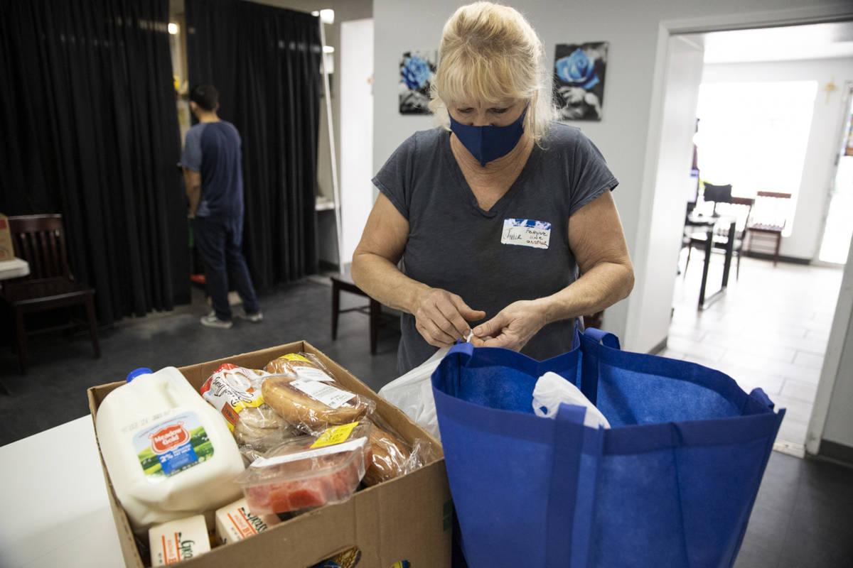 Volunteer Julie Presler puts together a box of food at the City Impact Urban Food Bank in Las V ...