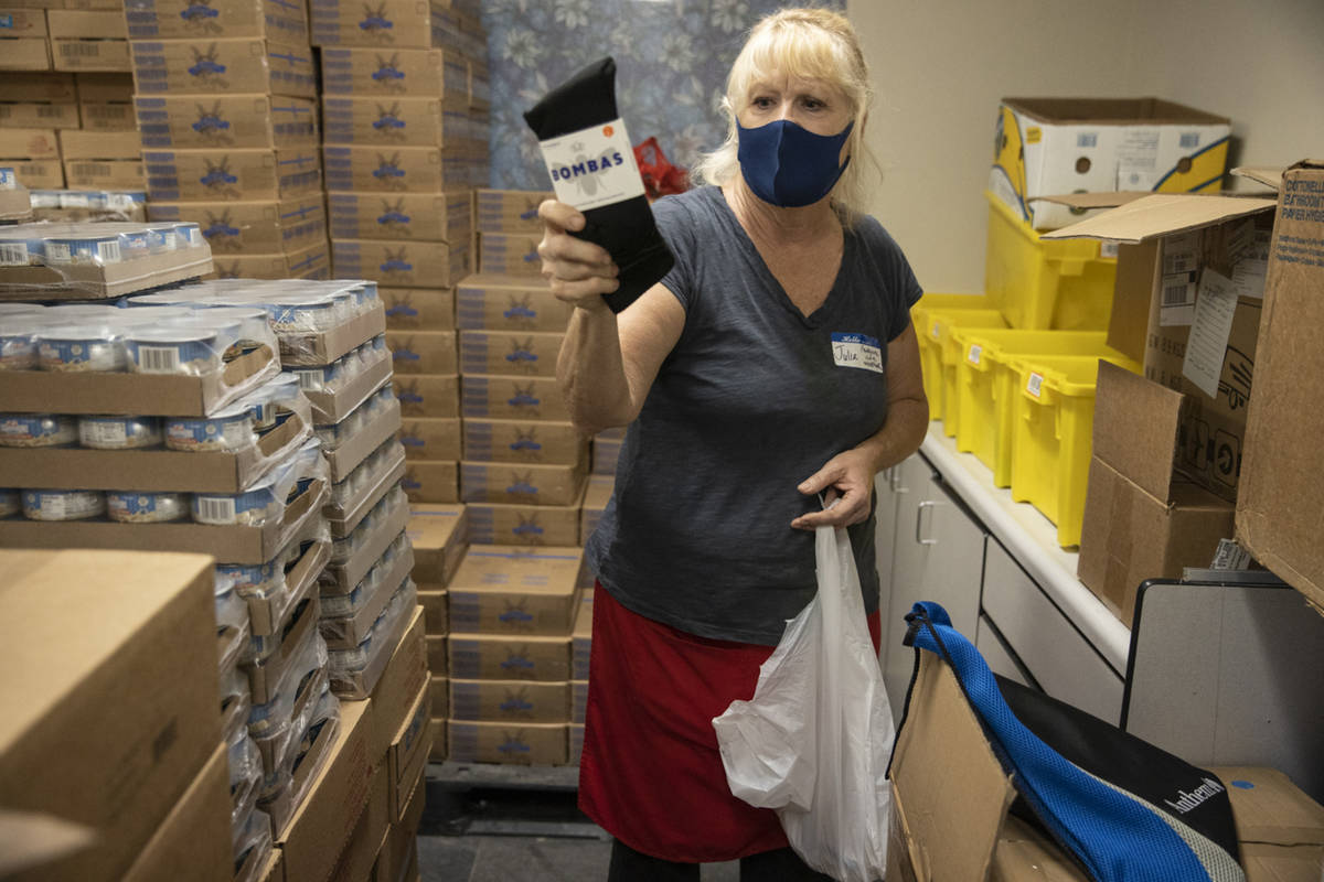 Volunteer Julie Presler puts together shows a pair of socks she included in a bag with other pe ...