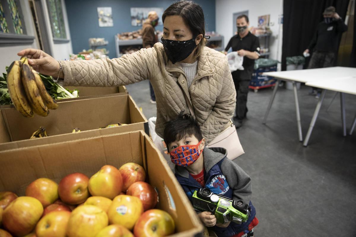 Yulissa Peña with her 4-year-old son Yadiel, selects bananas at the City Impact Urban Food ...