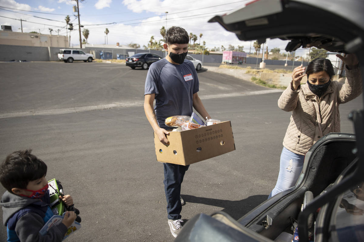 Volunteer Yahir Hernandez carries a box of food to the car of Yulissa Peña and her 4-year- ...