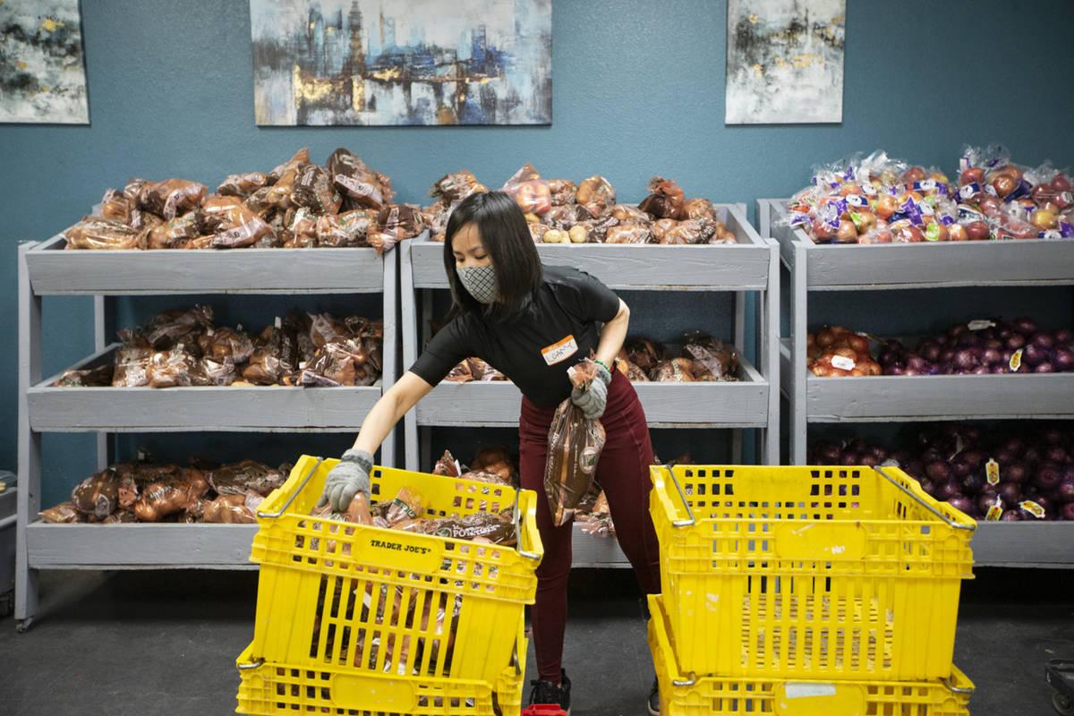 Volunteer Loan Ha organizes bags of potatoes at the City Impact Urban Food Bank in Las Vegas, o ...