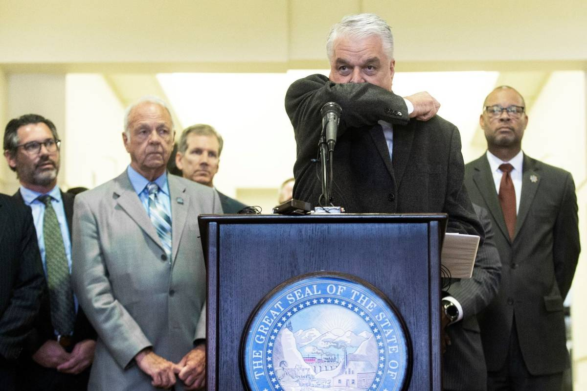 Governor Steve Sisolak demonstrates the best way to cough during a press conference at the Gran ...