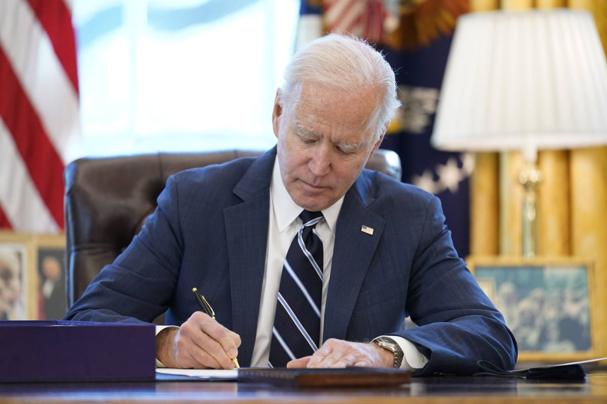 President Joe Biden signs the American Rescue Plan, a coronavirus relief package, in the Oval O ...