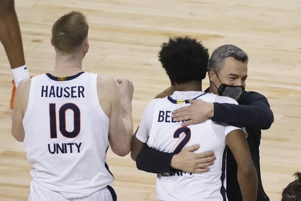 Virginia guard Reece Beekman (2) gets a hug from head coach Tony Bennett after sinking the game ...