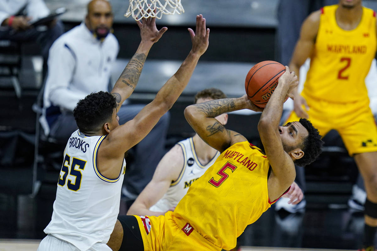 Maryland guard Eric Ayala (5) shoots over Michigan guard Eli Brooks (55) in the first half of a ...