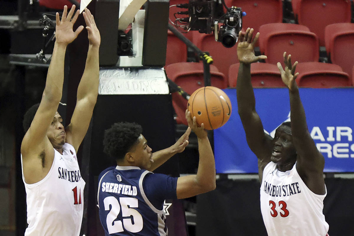 Nevada guard Grant Sherfield (25) passes as San Diego State forward Matt Mitchell (11) and forw ...