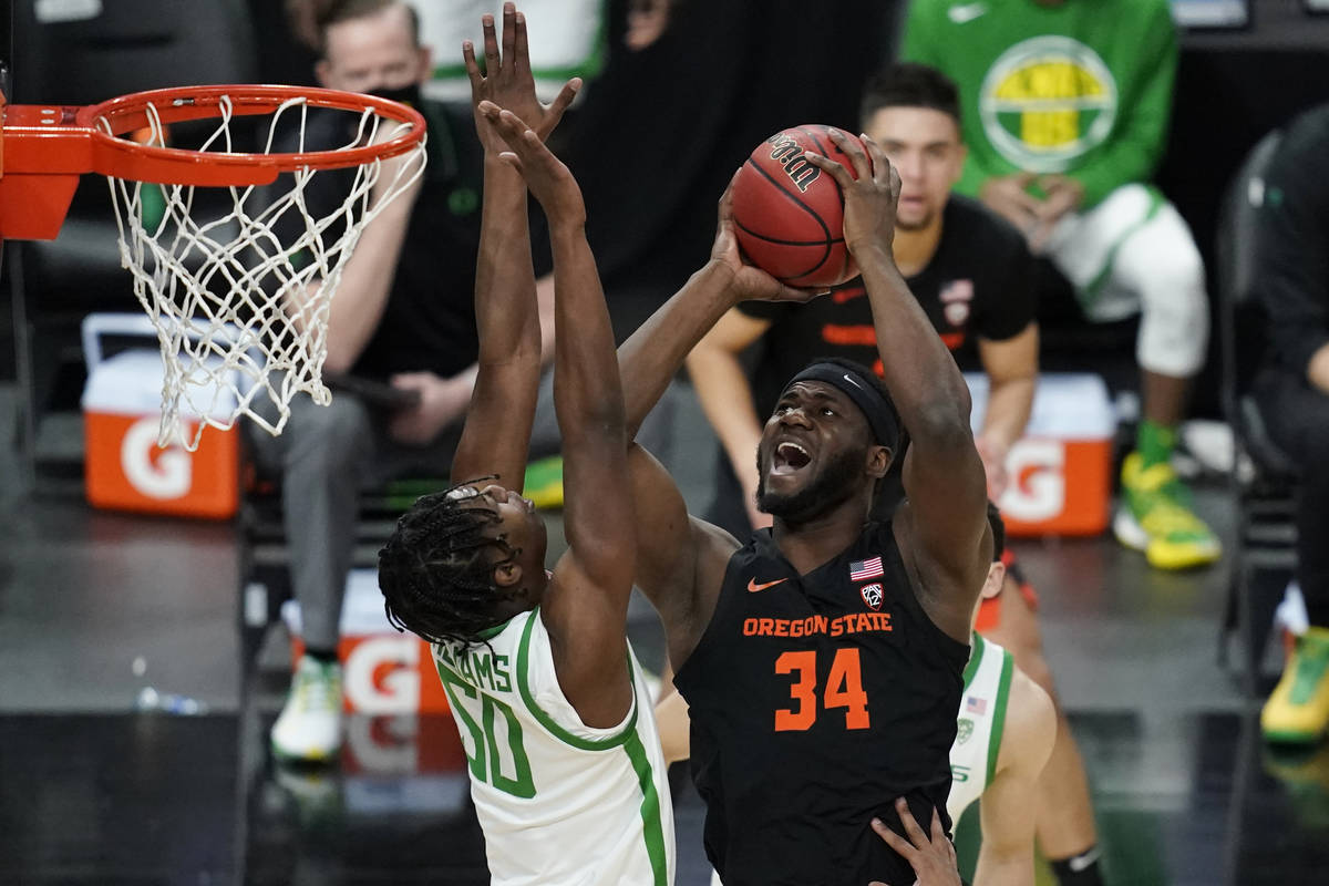 Oregon State's Rodrigue Andela (34) shoots over Oregon's Eric Williams Jr. (50) during the firs ...