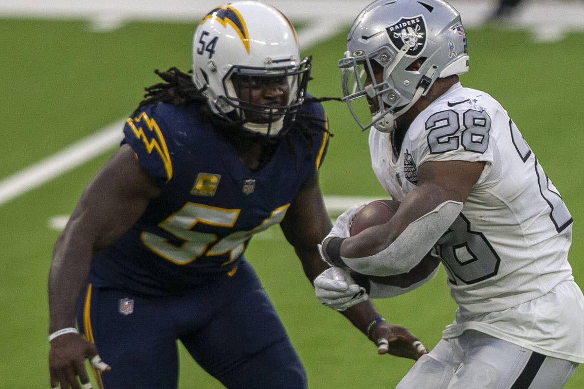 Las Vegas Raiders running back Josh Jacobs (28) tries to rush past Los Angeles Chargers defensi ...