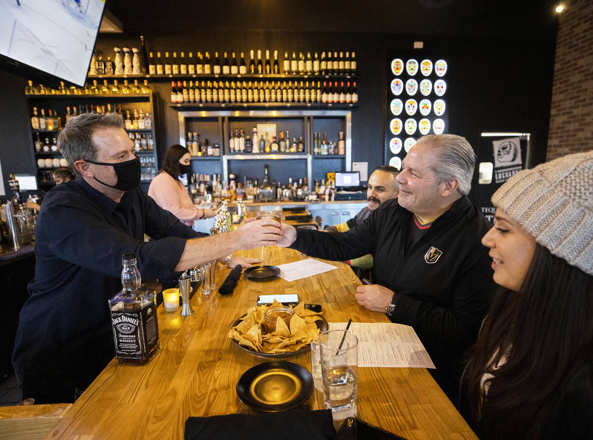 Andy Hooper, left, owner of El Luchador Mexican Kitchen + Cantina, serves a drink to John Engli ...