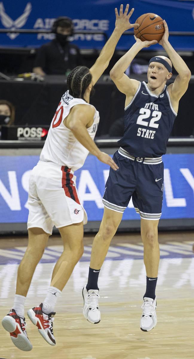 Utah State Aggies guard Brock Miller (22) shoots over San Diego State Aztecs guard Jordan Schak ...