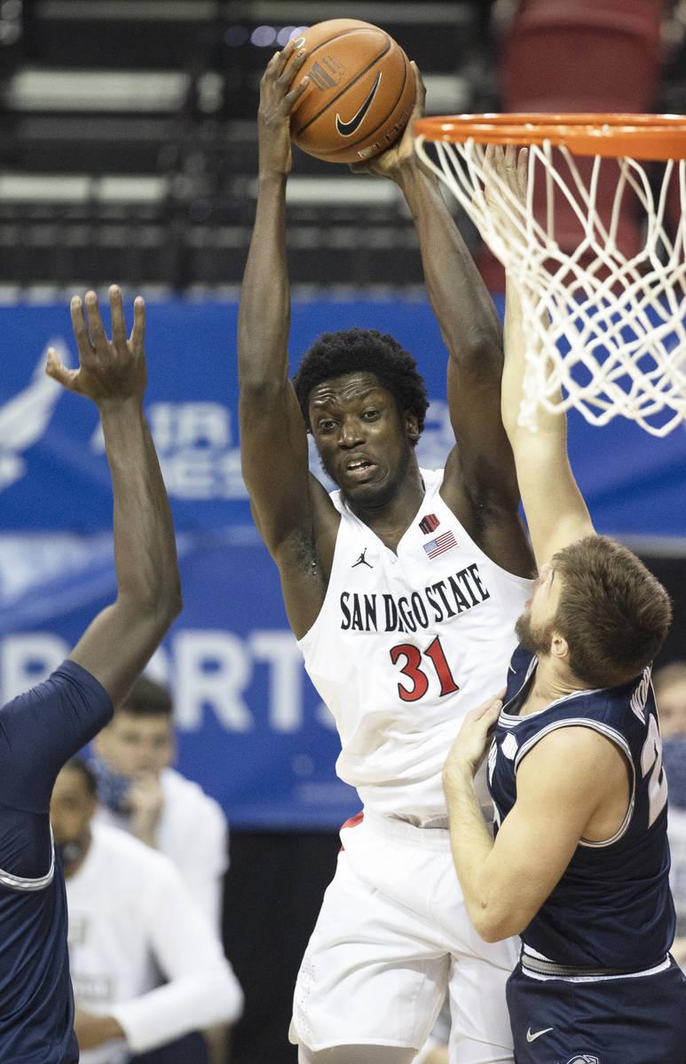 San Diego State Aztecs forward Nathan Mensah (31) grabs a rebound over Utah State Aggies guard ...